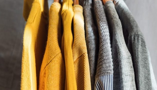 yellow-illuminated-color-and-gray-winter-sweaters-on-wooden-hangers-trendy-fashion-autumn-warm-and_t20_b62xJ6-750x430-1.jpg